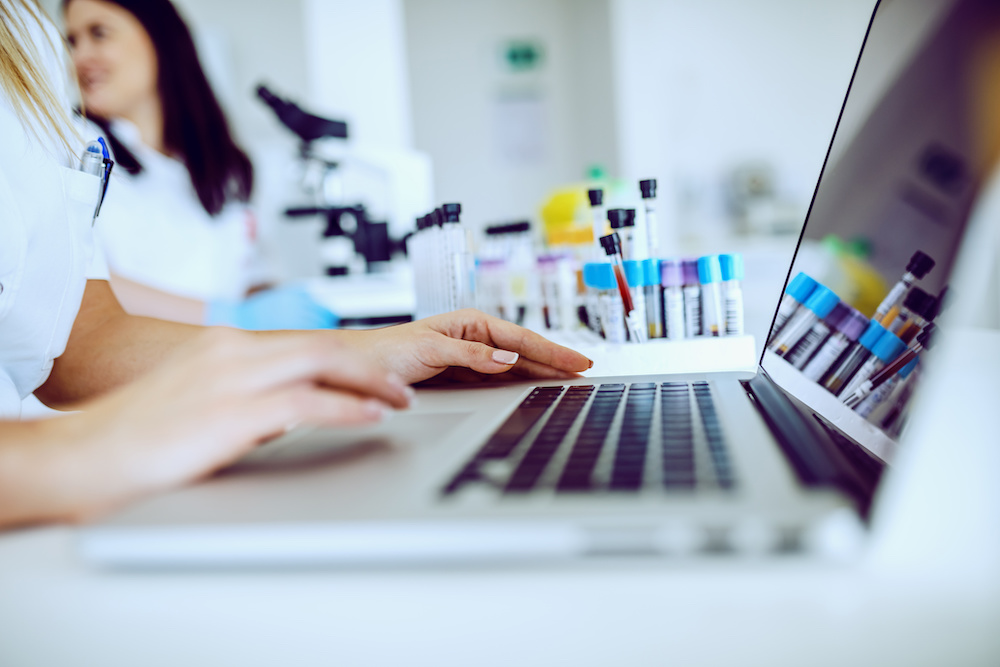 Close up of female lab assistant in white uniform sitting in lab and using laptop for data entry. In background is her colleague working.